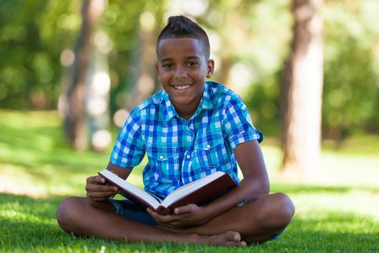 Outdoor portrait of student black boy reading a book - African p
